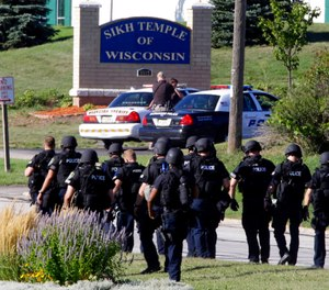 In this Aug. 5, 2012 photo, police walk near the Sikh Temple of Wisconsin in Oak Creek, Wis., after an active shooter killed six people. (AP Photo/Jeffrey Phelps, File)