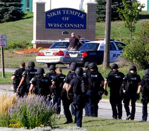 In this Aug. 5, 2012 photo, police walk near the Sikh Temple of Wisconsin in Oak Creek, Wis., after an active shooter killed six people.