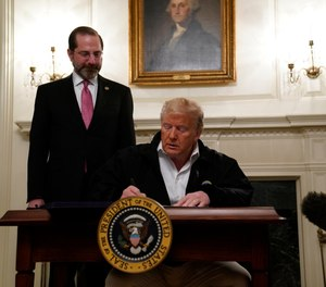 President Donald Trump signs an $8.3 billion bill to fight the coronavirus outbreak in the U.S., Friday, March 6, 2020 at the White House in Washington, as Department of Health and Human Services Secretary Alex Azar, looks on. The legislation provides federal public health agencies with money for vaccines, tests and potential treatments and helps state and local governments prepare and respond to the threat. (AP Photo/Evan Vucci)