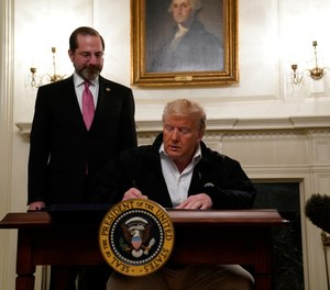 President Donald Trump signs an $8.3 billion bill to fight the coronavirus outbreak in the U.S., Friday, March 6, 2020 at the White House in Washington, as Department of Health and Human Services Secretary Alex Azar, looks on. The legislation provides federal public health agencies with money for vaccines, tests and potential treatments and helps state and local governments prepare and respond to the threat.