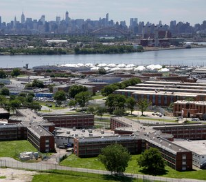 In a June 20, 2014, file photo, the Rikers Island jail complex stands in New York with the Manhattan skyline in the background. The nation's jails and prisons are on high alert about the prospect of the new coronavirus spreading through their vast inmate populations.