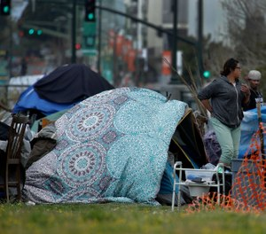 People are seen in a homeless encampment in Oakland, Calif. California Gov. Gavin Newsom has authorized $150 million in emergency funding to protect homeless people in California from the spread of COVID-19. (AP Photo/Ben Margot)
