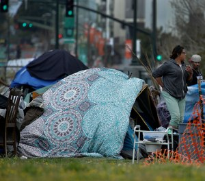 People are seen in a homeless encampment in Oakland, Calif. California Gov. Gavin Newsom has authorized $150 million in emergency funding to protect homeless people in California from the spread of COVID-19.