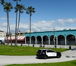 An LAPD patrol car drives through Venice Beach Boardwalk, Monday, March 23, 2020, in Los Angeles, afterthe boardwalk was officially closed Monday after widespread ignoring of social distancing over the weekend.
