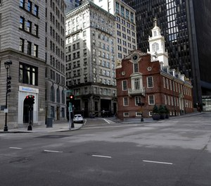 A passer-by walks through a nearly empty intersection near the Old State House, right, in downtown Boston, Tuesday, March 24, 2020.