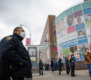 An NYPD officer wears personal protective equipment while maintaining order along a line to enter COVID-19 testing site at Elmhurst Hospital Center, Wednesday, March 25, 2020, in New York. (AP Photo/John Minchillo)