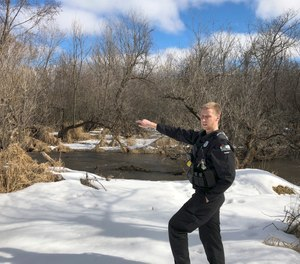 In this March 5, 2020 photo, Wisconsin Department of Natural Resources Warden Austin Schumacher stands on the edge of a marsh in Edgerton, Wis., where a 13-year-old boy disappeared after running away from school in November 2019. This month, Schumacher received the DNR's Lifesaving Award.