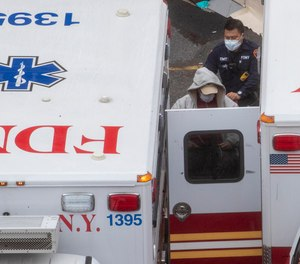 A paramedic transports a patient into the Trauma Center at the Elmhurst Hospital Center, Sunday, March 29, 2020, in the Queens borough of New York. FDNY EMS will be ordered not to transport cardiac arrest patients to the hospital if they cannot be resuscitated in the field, under a new rule made in response to overstretched hospital and ambulance resources due to COVID-19.