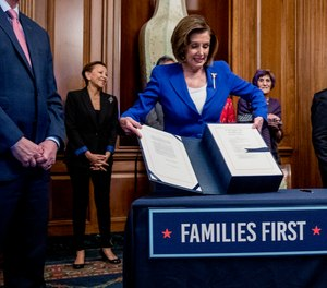 House Speaker Nancy Pelosi lifts the Coronavirus Aid, Relief, and Economic Security (CARES) Act after signing it on Capitol Hill, Friday, March 27, 2020, in Washington.