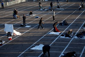 People prepare to sleep in areas marked by painted boxes on the ground of a parking lot at a makeshift camp for the homeless Monday, March 30, 2020, in Las Vegas. Image: AP Photo/John Locher
