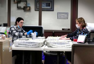 From left Katherine Katsekes, and Diane Scott, both paid volunteers, help sort absentee ballots by ward to be opened on election day at Brookfield City Hall, Tuesday, March 31, 2020. Image: Rick Wood/Milwaukee Journal-Sentinel via AP
