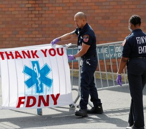 This photo from April 7, 2020, shows FDNY EMTs viewing a sign reading