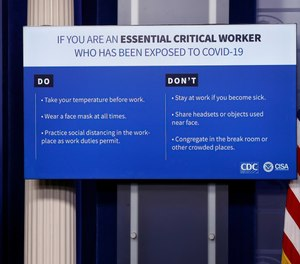 A chart outlining new guidelines by the CDC for essential workers is displayed during a briefing about COVID-19 in the James Brady Press Briefing Room of the White House, Wednesday, April 8, 2020, in Washington.
