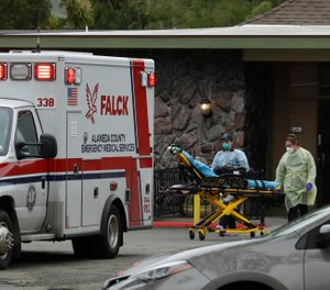 EMTs move a stretcher outside a nursing home in Hayward, Calif. Gov. Gavin Newsom has signed a bill that will give first responders who contract COVID-19 easier access to benefits under the state's workers' compensation program. (AP Photo/Ben Margot)