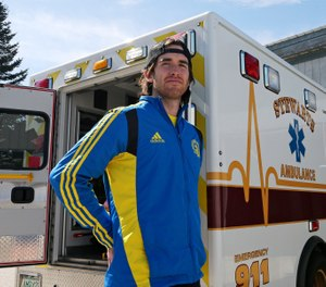 In this April 14, 2020 photo, Bobby O'Donnell, a Boston Marathon bombing survivor and currently a paramedic, poses at his ambulance's base of operations in Meredith, N.H. O'Donnell has been transporting COVID-19 patients to hospitals in the state's Lakes region. (AP Photo/Charles Krupa)