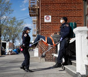 FDNY paramedics Elizabeth Bonilla, left, and Keith Kahara, right, carry a patient from her home to their ambulance on an emergency call, Wednesday, April 15, 2020, in the Bronx borough of New York. (AP Photo/John Minchillo)