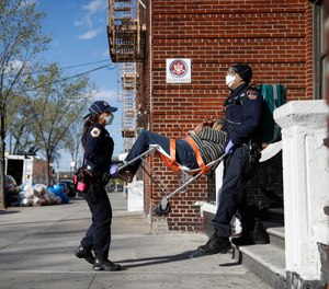FDNY paramedics Elizabeth Bonilla, left, and Keith Kahara, right, carry a patient from her home to their ambulance on an emergency call, Wednesday, April 15, 2020, in the Bronx borough of New York.