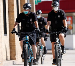 Denver Police Department officers wear face masks as they patrol on their bicycles in Denver on April 22, 2020.