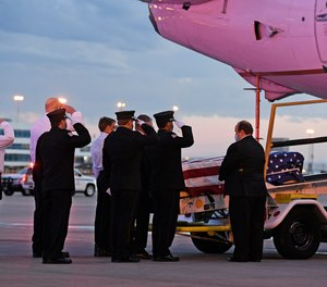 Ambulnz paramedics and Aurora firefighters salute as the casket carrying the body of paramedic Paul Cary is removed from a plane at Denver International Airport on Sunday, May 3, 2020, in Denver. Cary died from coronavirus after volunteering to help combat the pandemic in New York City.