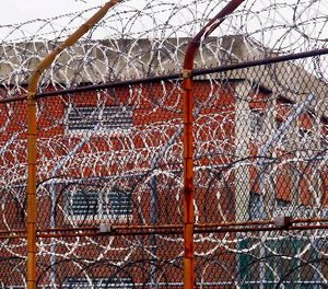 A security fence surrounds inmate housing on the Rikers Island correctional facility in New York. (AP Photo/Bebeto Matthews)