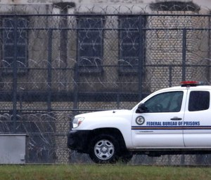 A Federal Bureau of Federal Prisons truck drives past barbed wire fences at the Federal Medical Center prison in Fort Worth, Texas. (AP Photo/LM Otero)
