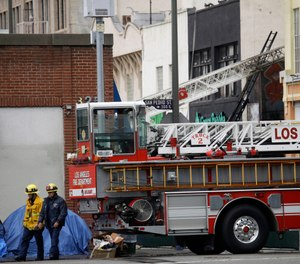 Firefighters walk the scene of a fire and explosion at a smoke and vape wholesale business on Monday, May 18, 2020, in Los Angeles. The Fire Department was at the nondescript commercial building late Saturday afternoon when there was a thunderous explosion that sent firefighters scrambling through searing flames to get out of the building. The department now plans to conduct a citywide review to examine how similar businesses store volatile materials. (AP Photo/Marcio Jose Sanchez)