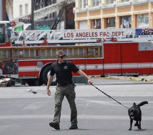 A search dog is used at the scene of a fire and explosion Monday, May 18, 2020, in Los Angeles. The Fire Department was at the nondescript commercial building late Saturday afternoon when there was a thunderous explosion that sent firefighters scrambling through searing flames to get out of the building. Twelve firefighters were injured. All are expected to survive.