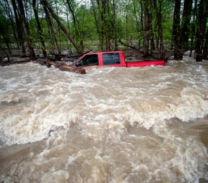 Tittabawassee Fire and Rescue rescued the driver from this red pickup truck in Saginaw County, Mich. The truck was swept off of the road by standing water. (Photo/Jake May, The Flint Journal via AP)
