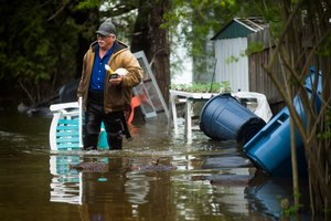 Mark Musselman brings a chair to the front of his house from the back yard, wading through floodwater, Tuesday, May 19, 2020 in Edenville, Mich. Image: Katy Kildee/Midland Daily News via AP