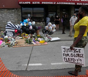 Protesters gather at a makeshift memorial in Minneapolis near the site where George Floyd was taken into police custody before he died.