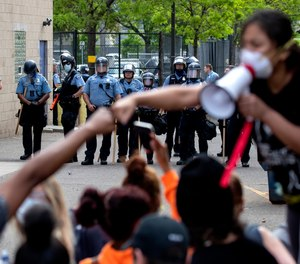 People gather in front of Minneapolis police officers Wednesday, May 27, 2020, as they protest the arrest and death of George Floyd.