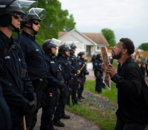 A demonstrator stands in front of police officers outside the home of fired Minneapolis police Officer Derek Chauvin on Wednesday evening, May 27, 2020. (Jeff Wheeler/Star Tribune via AP)