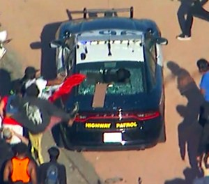 Protesters attack a CHP cruiser during a Black Lives Matter protest on a freeway in downtown Los Angeles on Wednesday, May 27, 2020. Hundreds of people protesting the death of a black man in Minneapolis police custody blocked the freeway. (KABC-TV via AP)