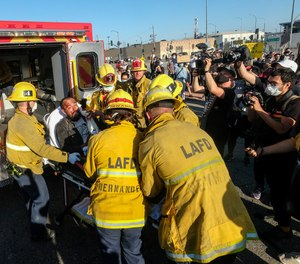 Los Angeles firefighters transfer a demonstrator to an ambulance during a protest.