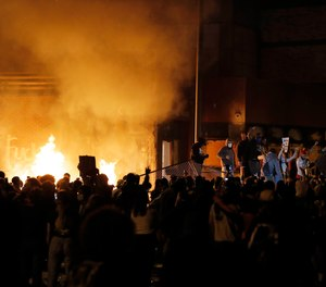 Crowds gather in front of the burning Minneapolis police 3rd Precinct building Thursday, May 28, 2020, in Minneapolis.
