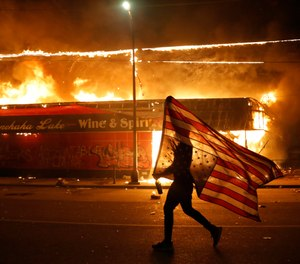 A protester carries a U.S. flag upside down, a signal of distress, next to a burning building Thursday, May 28, 2020, in Minneapolis. (AP Photo/Julio Cortez)