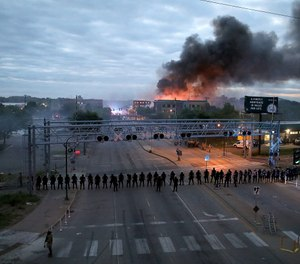 Law enforcement officers amassed along Lake Street near Hiawatha Ave. as fires burned after a night of unrest and protests in the death of George Floyd early Friday, May 29, 2020 in Minneapolis. (Photo/David Joles, Star Tribune via AP)