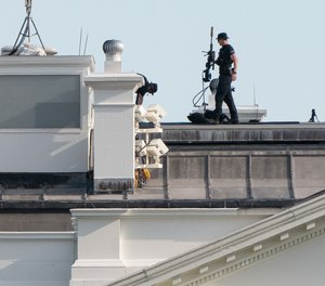 A U.S. Secret Service counter-sniper team looks out from atop the White House.