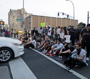 Protesters sit at an intersection during a protest over the deaths of George Floyd and Breonna Taylor, Saturday, May 30, 2020, in Louisville, Ky.
