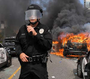 Los Angeles Police Department commander Cory Palka stands among several destroyed police cars as one explodes while on fire during a protest over the death of George Floyd, Saturday, May 30, 2020, in Los Angeles. (AP Photo/Mark J. Terrill)