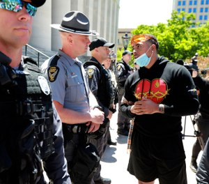 Jalon Lewis talks with Ohio State Trooper Weaver (no first name given) at the Ohio Statehouse in Columbus during a peaceful Sunday, May 31, 2020 protest over the death of George Floyd in Minnesota. (Doral Chenoweth/The Columbus Dispatch via AP)