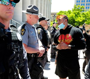Jalon Lewis talks with Ohio State Trooper Weaver (no first name given) at the Ohio Statehouse in Columbus during a peaceful Sunday, May 31, 2020 protest over the death of George Floyd in Minnesota.