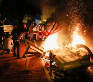 Demonstrators start a fire during a protest over the killing of George Floyd, Sunday, May 31, 2020, near the White House in Washington.