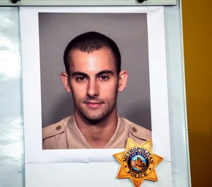 A photo of Las Vegas police officer Shay K. Mikalonis, 29, a four-year veteran of the department, is displayed during a media briefing at police headquarters in Las Vegas on Tuesday, June 2, 2020. (Steve Marcus/Las Vegas Sun via AP)