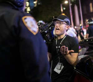 """Associated Press videojournalist Robert Bumsted reminds a police officer that the press are considered """"essential workers"""