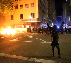 In this May 29, 2020, photo, a protester faces police officers in downtown in Portland, Ore. On May 30, the city's 911 system hit a 25-year record number of calls as civil unrest peaked over the killing of George Floyd.
