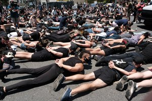 LGBTQ community members join Black Lives Matter demonstrators lie face down depicting George Floyd during his detention by police, blocking an intersection in protest over Floyd's death, in West Hollywood, Calif., on Wednesday, June 3, 2020. Image: AP Photo/Richard Vogel
