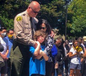 Santa Cruz Sheriff Jim Hart stands next to fallen Sgt. Damon Gutzwiller's pregnant widow and child, as more than a thousand people gather outside the Santa Cruz County Sheriff-Coroner's Office to pay their respects in Santa Cruz, Calif., Sunday, June 7, 2020.(AP Photo/Martha Mendoza)