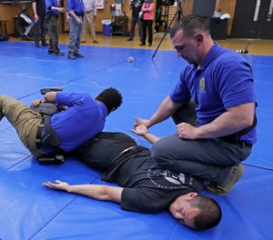 Washington State Criminal Justice Training Commission instructors conduct a demonstration of takedown and restraint techniques, which are part of the more than 700 hours of training police and other officers are required to go through in the state. (AP Photo/Ted S. Warren)