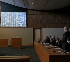 The photos of the 84 people killed in the 2018 Camp Fire are displayed as Bill Johnson, CEO and president of PG&E Corp., right, stands as the charges are read against the company's action that caused the fire.